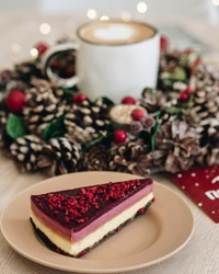 A piece of cake is on a plate. Christmas wreath for home decoration. in the center there is a mug with cappuccino coffee. A heart is drawn on the foam. Warming Christmas drink. Veggie sweets for Chris