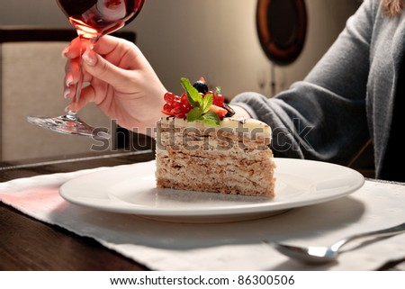 A piece of cake with forest berries decorated with mint leaf on a white plate in a restaurant, a woman sitting, holding a glass of wine - stock photo