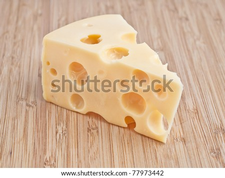 a piece of cheese with holes on a wooden board