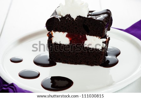A piece of chocolate cake with white cream chocolate sauce and strawberry filling on white plate