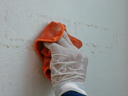 A piece of cloth, soaked with thinner, in a hand of a painter being used to remove sticky rough glue and tape remain on the old concrete wall, as a preparation before starting to paint the house