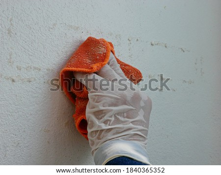 A piece of cloth, soaked with thinner, in a hand of a painter being used to remove sticky rough glue and tape remain on the old concrete wall, as a preparation before starting to paint the house Stock photo ©