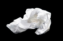 A piece of crumpled white paper on a black background.