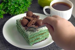 A piece of delicious green pear cake decorated with chocolate and sweets is broken off with a spoon from a large piece on a white plate close-up, on a blurred background, a cup, a pear, a plant.