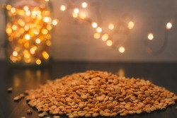 A piece of dried yellow peas for making soup or a side dish. Glass jar with yellow Christmas lights in the background. Dry seeds of legumes