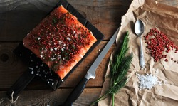 A piece of fresh salmon on a dark board. The fish is sprinkled with sea salt, pink pepper and dill. Next to kraft paper salt, pepper, dill. In the frame is a knife. Wooden background. View from above.