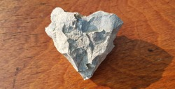 A piece of gray hardened cement in the shape of a heart, on a brown wooden table (top view).