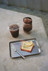 A piece of lemon cake, black coffee and a iced chocolate in the coffee shop.