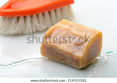 A piece of Marseille soap and an orange brush on the sink with water
