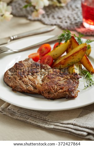 a piece of pork with sauteed potatoes and tomatoes on awhite plate #372427864