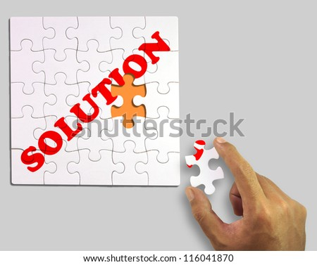A piece of puzzle in hand. to complete the word solution (Clipping Path)
