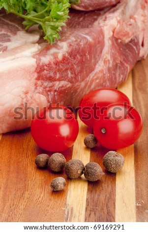 A piece of raw meat on a multilayer wooden kitchen cutting board.