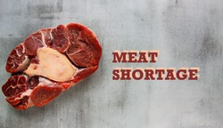 A piece of raw meat with a bone on marble background. Shortages of beef, pork and chicken meat in some countries due to the pandemic of coronavirus COVID-19. Text: Meat shortage
