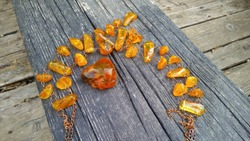 A piece of sparkling Baltic yellow raw natural amber and a wonderful amber necklace on an old, weathered wooden bench in the abandoned ruined boat.