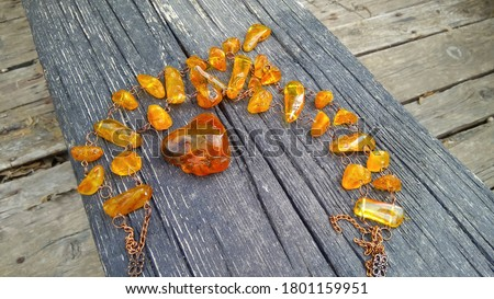 A piece of sparkling Baltic yellow raw natural amber and a wonderful amber necklace on an old, weathered wooden bench in the abandoned ruined boat. Сток-фото ©