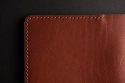 a piece of stitched brown leather on a black background with free space for an inscription. Leather craft concept.