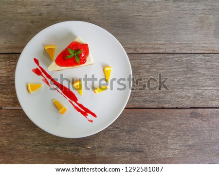 A piece of strawberry cheesecake cake on a white plate and brown wood background. Top view picture concept