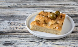 A piece of traditional Italian food-focaccia in a white plate on a beautiful wooden table with an unusual texture. Focaccia consists of flour, olive oil, water, yeast, rosemary, sugar and Fleur de Sel