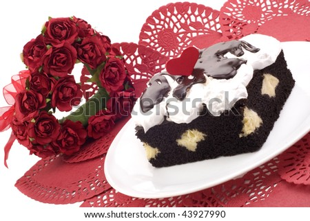 A piece of Valentine's Chocolate Cream Cake with Valentine's decorations, white background with copy space, horizontal