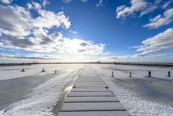 A pier in the sea by the entrance to the port with frozen sea and snow, in the background blue sky, sun and white clouds, ultra wide angle of view.