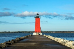 A pier leads up to the bright red Manistique Lighthouse, and landmark on the Lake Michigan coast of the Upper Peninsula of Michigan.