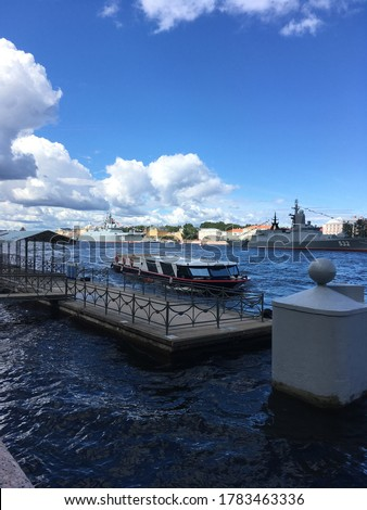 A pier, to which a pleasure boat approaches, followed by warships in the water area of ​​the Neva, arrived to participate in a naval parade in St. Petersburg.