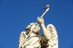 A pigeon enjoying a sunny Roman day on top of a spear.