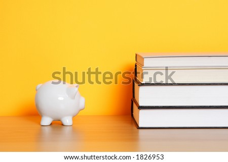 "A piggy bank and a stack of books, can be used for ""saving for college"" design"
