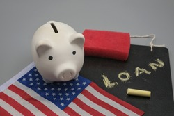 A piggy bank on a flag of the United States of America and a black chalkboard with the words, loan, with a sponge to a erase and a chalk. Student debt cancellation concept