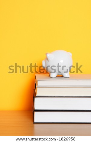 A piggy bank on top of a stack of books, can be used for saving for college design