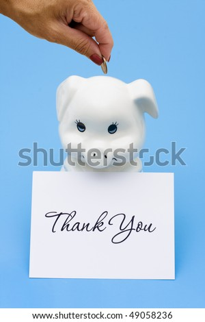A piggy bank sitting with a thank you card on a blue background, thank you for saving - stock photo