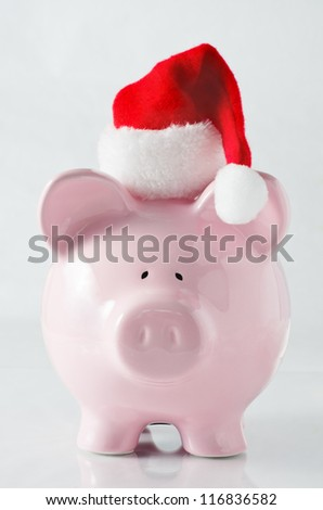 A piggy bank wearing a santa hat to signify saving money to plan ahead for the cost of Christmas.