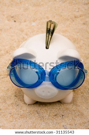 A piggy bank wearing swimming goggles on a sand background, vacation savings