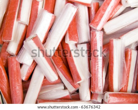 A pile of beautiful crab sticks on a counter - stock photo
