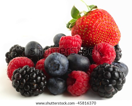 A pile of berry fruits, blueberries, raspberries, blackberries and a strawberry, against a white background.