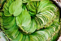 A pile of betel nut leaves arranged in the usual circular patten at market in Bagan