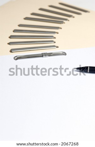 A pile of blank files lays on a desk with a pen