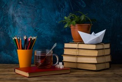 A Pile of Books, A Cup of Hot Tea, A Paper Boat, Colored Pencils on a Darkly Blue Background.
