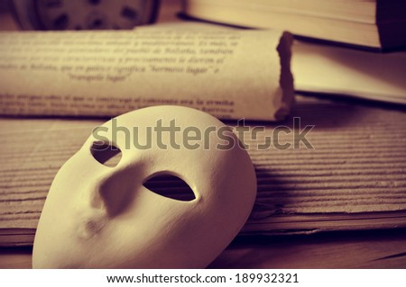a pile of books and a mask ...