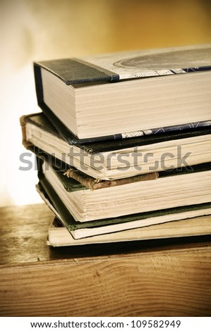 a pile of books on a desk symbolizing the concept of reading habit or studying - stock photo