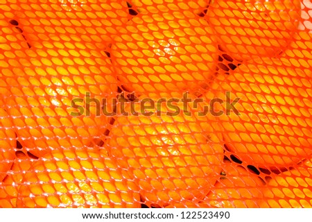 A pile of brightly orange clementines or mandarins under a red plastic mesh for protection during transport.