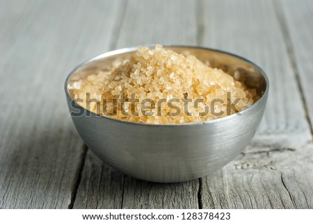 a pile of brown sugar in steel bowl, weathered wooden table background