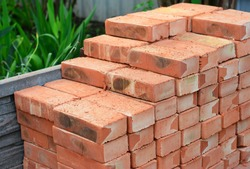 A pile of building materials, stack of new red bricks for construction are accurately put together.