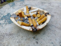 A pile of cigarette butts and ashes in an ashtray with blur effect
