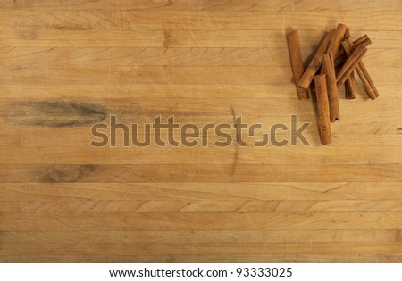 A pile of cinnamon sticks sits on a worn counter top
