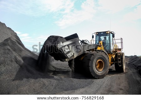 A pile of coal ore with a front end loader