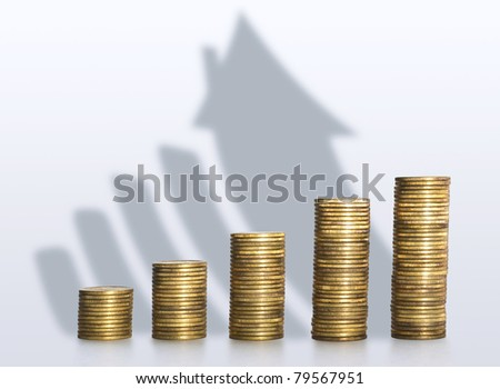 A pile of coins casting a shadow as house, savings concept