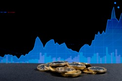 a pile of coins on a black background against the background of a trading chart, an upward trend, a bullish trend, the concept of accumulating finance and profit.
