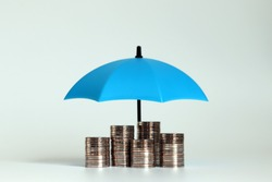 A pile of coins with an open blue umbrella.