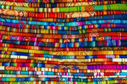 A pile of colorful Andean textiles photographed in the local handicraft market of Cusco, Peru.